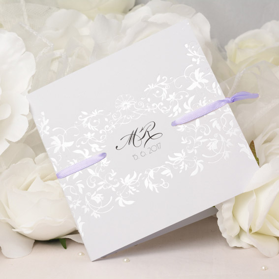 Opening elegant wedding invitation with a pearl embossed ornament